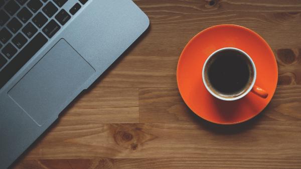 Zeigt einen Laptop und eine Tasse Kaffee